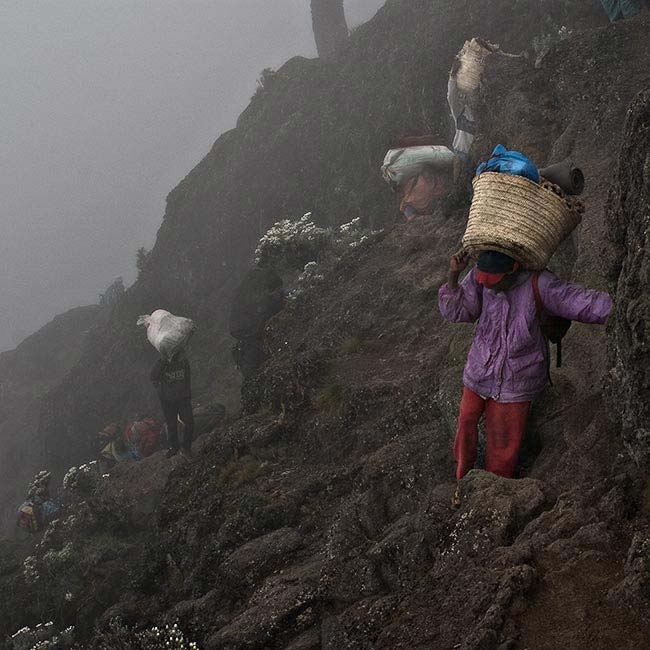 Porters carrying loads. (Photo: Adam Angel)