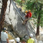 Instructor Olivia Race demonstrating a tandem lower - rappelling with an injured climber. (Photo by George Dunn)