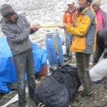 Tibetan Porters weighing the last of the gear to be removed from the mountain