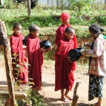 Monks receiving rice from women in village (Jenni Fogle)