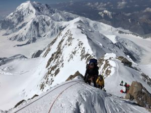 Climbing on the West Buttress with Mt Foraker behind (Eric Simonson)
